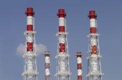 Cinco tubos industriales del color en el cielo azul Foto de archivo