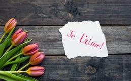 Cinco tulipas brilhantes em uma tabela de madeira Fotos de Stock Royalty Free