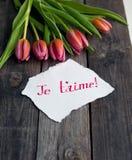 Cinco tulipas brilhantes em uma tabela de madeira Imagens de Stock Royalty Free