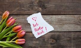 Cinco tulipas brilhantes em uma tabela de madeira Foto de Stock Royalty Free