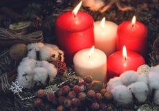 Cinco velas ardientes con las bayas y la nieve del algodón Fotografía de archivo libre de regalías