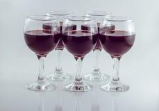 Cinco vidrios de cristal transparentes de vino rojo de la uva fotografía de archivo