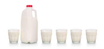 Cinco vidrios de leche por la botella plástica en blanco Imagen de archivo libre de regalías