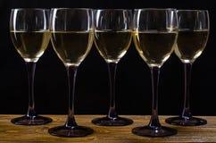 Cinco vidrios de vino blanco en la tabla Imagenes de archivo
