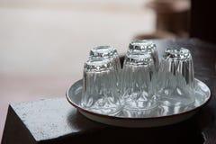 cinco vidrios vacíos pusieron al revés en la bandeja blanca en la tabla de madera w Imagen de archivo libre de regalías