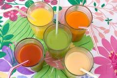 Cinco vidros de vários sucos com palhas fotografia de stock royalty free