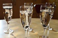 Cinco vidros de vinho espumante do champanhe encheram-se com o champanhe e as uvas-do-monte congeladas que fazem bolhas visualmen Foto de Stock