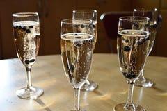 Cinco vidros de vinho espumante do champanhe encheram-se com o champanhe e as uvas-do-monte congeladas que fazem bolhas visualmen Imagens de Stock