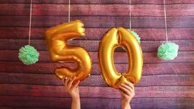 Cincuenta cumpleaños feliz con los balones de aire de oro del número 50, celebración del aniversario metrajes