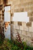 Cinder block building with white rusty door Stock Photo