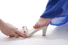 Cinderella shoe. Cinderella's shoe concept - prince's hand giving the shoe to cinderella to try it on Royalty Free Stock Image