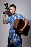Cineasta del hombre joven con la cámara de película vieja y una maleta en el suyo fotografía de archivo libre de regalías