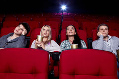 At cinema. Satisfied girls and bored boys watching a movie at the cinema Royalty Free Stock Photography