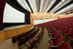 Cinema. Empty cinema hall, white screen, velvet seats Stock Photo