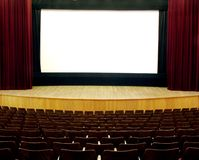 Cinema. Wooden seats and stage, red velvet curtain, white empty screen Royalty Free Stock Image