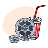 Cinema attributes, film reel and soda water in paper cup Royalty Free Stock Photography