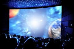 Cinema. The audience in 3D glasses watching a movie. Elements of this image furnished by NASA Royalty Free Stock Photos
