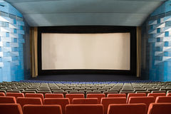 Cinema auditorium. Empty cinema auditorium with line of chairs and stage with projection screen. Ready for adding your own picture Stock Images