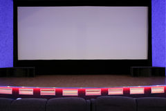 Cinema auditorium. Empty blue cinema auditorium with red stage and projection screen. Ready for adding your own picture Royalty Free Stock Image