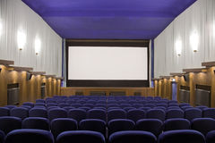 Cinema auditorium. Empty cinema auditorium with line of chairs and projection screen. Ready for adding your own picture. Front view Royalty Free Stock Photos