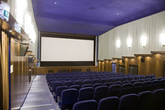 Cinema auditorium. Empty cinema auditorium with line of chairs and projection screen. Ready for adding your own picture. Left side view Royalty Free Stock Photos