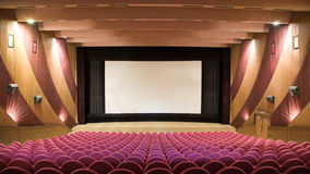 Cinema auditorium. Empty cinema auditorium with line of pink chairs and projection screen. Ready for adding your own picture Stock Photo