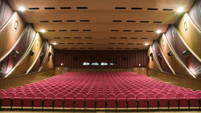 Cinema auditorium. Interior of cinema auditorium with walls and ceilling decoration and line of pink chairs Royalty Free Stock Photos
