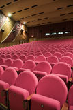Cinema auditorium. Interior of cinema auditorium with walls and ceiling decoration and line of pink chairs Royalty Free Stock Photos