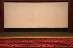 Cinema auditorium. Empty cinema auditorium with line of red chairs and projection screen. Ready for adding your own picture Royalty Free Stock Photography