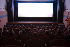 Cinema auditorium with people. In chairs watching movie performance. Ready for adding your own picture Royalty Free Stock Photo