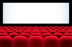Cinema auditorium with rows of red seats and blank screen Stock Images