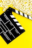 Cinema background. Film watching. Popcorn and clapperboard on yellow background top view copy space. Cinema background. Film watching. Popcorn and clapperboard stock image