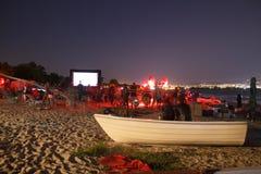 CINEMA ON THE BEACH AT NIGHT. MOVIE CINEMA ON THE BEACH WITH CITY BEHIND Stock Photos