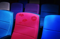 Cinema chair. A red cinema chair with some red lip prints on it stock photo