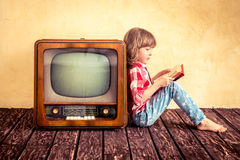 Cinema. Child playing at home. Kid reading the book near retro TV. Cinema concept Stock Image