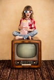Cinema. Child playing at home. Kid sitting on retro TV and eating popcorn. Cinema concept Royalty Free Stock Image