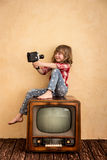 Cinema. Child playing at home. Kid taking selfie with retro camera. Cinema concept Stock Image