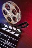 Cinema clapboard and reel on black stone Royalty Free Stock Photos