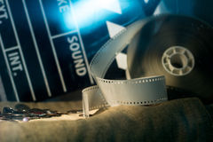 Cinema clapper and video film negative movie on a rough cloth. Stock Photography