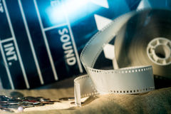 Cinema clapper and video film negative movie on a rough cloth. Coins lying on the fabric stock image
