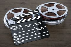 Cinema concept. Clapperboard with film reels on the wooden table. 3D stock images