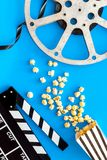 Cinema concept. Clapperboard, film stock, popcorn on blue background top view royalty free stock photo