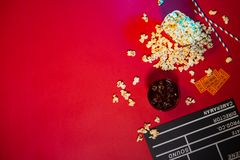 Cinema concept. Clapperboard, ticket and popcorn on red background stock image