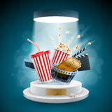 Cinema Concept Design. Popcorn box; disposable cup for beverages with straw, film strip, clapper board and ticket on the podium. Cinema Concept Design. Detailed Stock Image