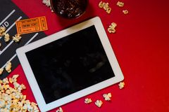 Cinema concept. Digital tablet screen with clapperboard, ticket Stock Photography