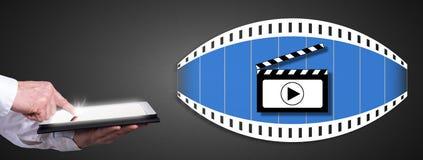 Cinema concept with man using a tablet. Man using a tablet with cinema concept Royalty Free Stock Photos