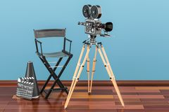 Cinema concept. Movie camera with film reels, chair, megaphone a. Nd clapperboard on the wooden floor Royalty Free Stock Image