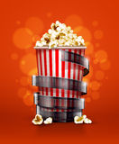 Cinema concept with paper bucket with popcorn and film tape Royalty Free Stock Photo