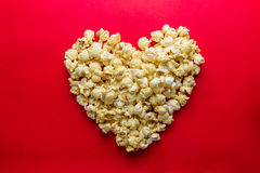 Cinema concept of popcorn arranged in a heart shape on red backg Royalty Free Stock Photo