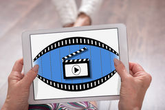 Cinema concept on a tablet. Cinema concept shown on a tablet held by a woman Royalty Free Stock Image